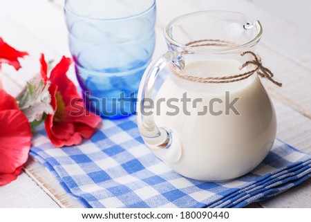 Milk in pither on white wooden table. Selective focus.