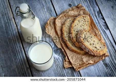 Milk in tall bottle and glass placed next to slices of bread with seeds over wooden background