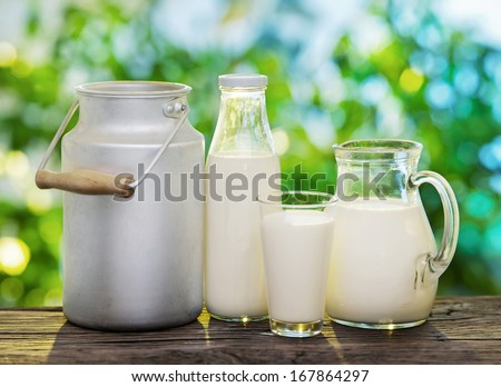Milk in various dishes on the old wooden table in an outdoor setting.