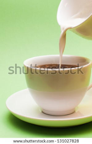milk is poured into a white porcelain cup with coffee - stock photo