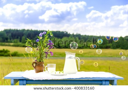 Milk jug and glass on wooden table. On a background of the summer sky with clouds.