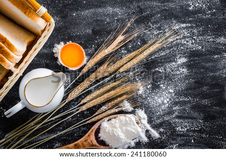 milk jug, bread and products for baking on a black  textured table - stock photo