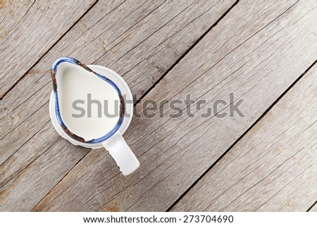 Milk jug on wooden table. View from above with copy space - stock photo
