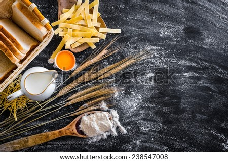 milk jug, pasta and products for baking on a black  textured table - stock photo