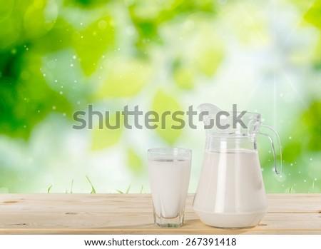 Milk. Milk on table and sunny trees - stock photo