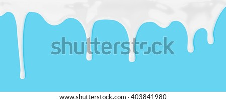 milk or white liquid dripping on blue background - stock photo