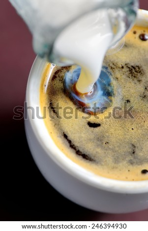 Milk poured into small cup of coffee. view of above - stock photo