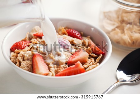 milk pourin g in cereal with strawberry for breakfast