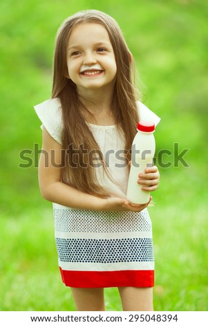 Milk products concept. Baby girl with long brown hair in white vintage summer dress drinking yogurt in the park, holding white plastic bottle. Outdoor shot - stock photo