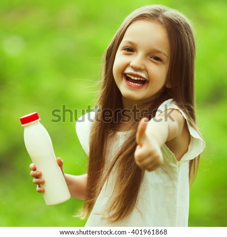 Milk products concept. Baby girl with long brown hair in white vintage summer dress drinking yogurt in the park, holding white plastic bottle, showing thumb up. Milk mustache under nose. Outdoor shot