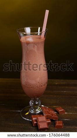 Milk shake on table on dark yellow background - stock photo