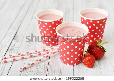 Milk shake with fresh berries and straws on wooden background - stock photo