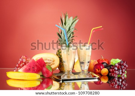 Milk shakes with fruit on red background close-up - stock photo