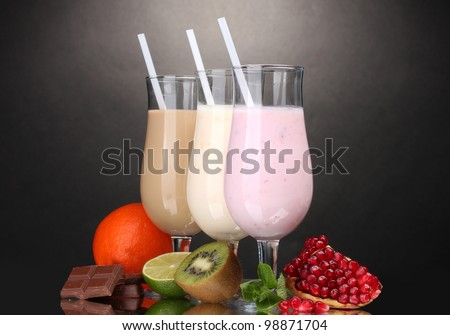 Milk shakes with fruits and chocolate on grey background - stock photo
