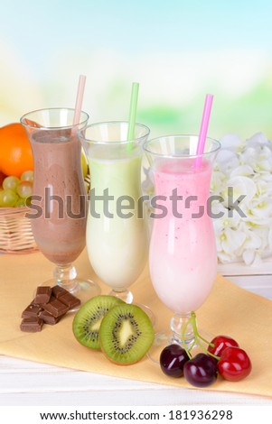 Milk shakes with fruits on table on light blue background - stock photo