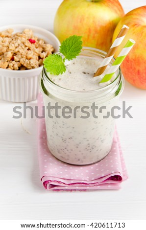 Milk smoothies with chia seeds in glass jar, apples, and muesli on white wooden background