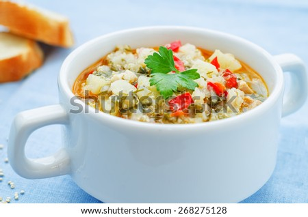 milk soup with potatoes, quinoa and peppers on a blue background. the toning. selective focus - stock photo