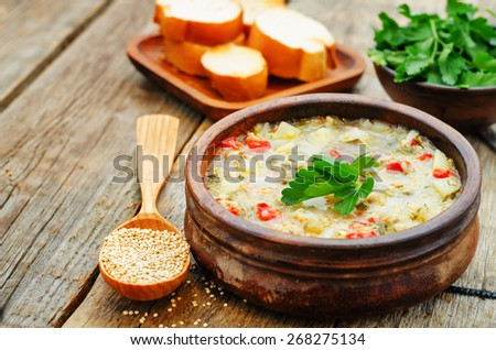 milk soup with potatoes, quinoa and peppers on a dark wood background. the toning. selective focus - stock photo