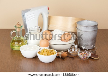 Milk, sour cream, flour, raisin and spices for an Easter cake, on a beige background