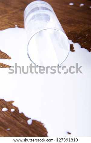 Milk spilled from glass on wooden surface - stock photo