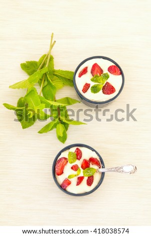 Milk strawberries dessert. Fresh red strawberries with cream and mint on white table. Easy dietary breakfast. Dessert food photography. - stock photo