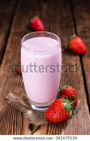 Milk (Strawberry flavoured) on wooden background (selective focus) - stock photo