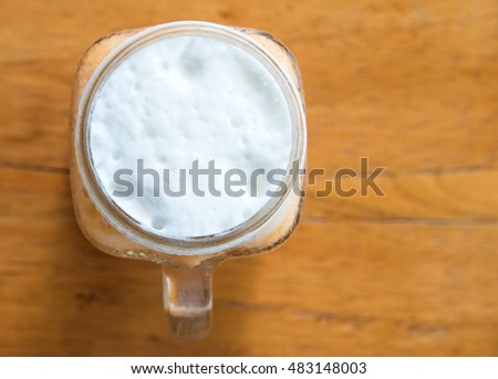 Milk tea with ice in Glass handle on wooden table,Top view focus.Milk glass top.