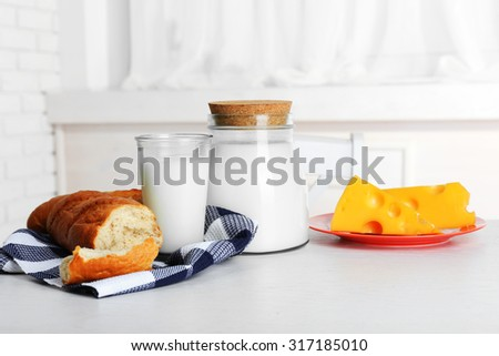 Milk with bread and cheese on table in kitchen