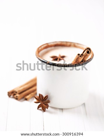Milk with cinnamon and anise in rustic mug on white wooden table - stock photo