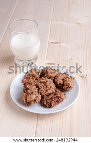Milk  with cookies baked with oat, chocolate and dried fruits - stock photo