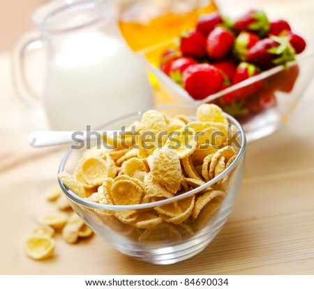 milk with corn flakes on wood