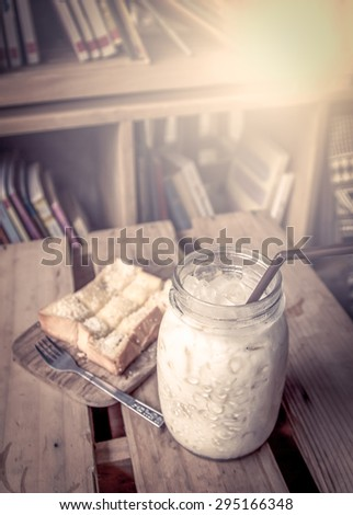 milk with toast on wooden table with books in vintage color tone - stock photo