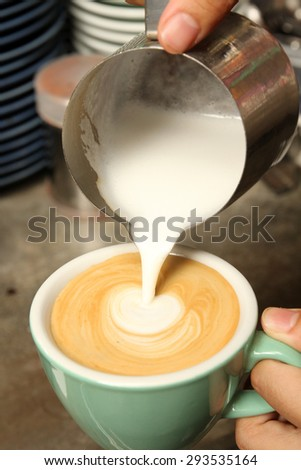Milking being poured into cup of coffee - stock photo