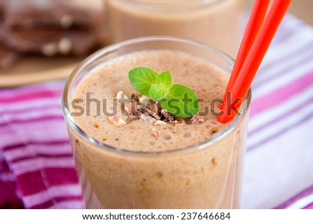 Milkshake (chocolate and banana smoothie) in glass with mint and nuts, homemade dairy breakfast horizontal close up - stock photo