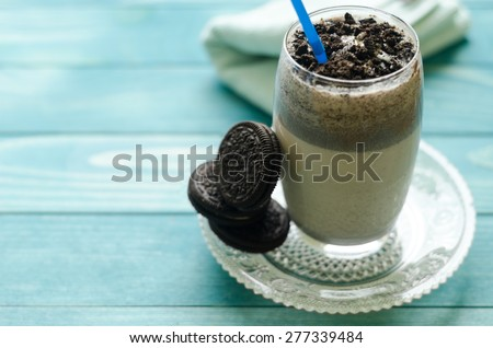 Milkshake (chocolate smoothie)  in a glass on colorful turquoise blue painted wooden boards. Selective focus on cookies in glass - stock photo