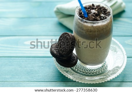 Milkshake (chocolate smoothie)  in a glass on colorful turquoise blue painted wooden boards. Selective focus on cookies - stock photo