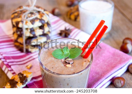 Milkshake (chocolate smoothie) in glass with mint, nuts and homemade cookies, breakfast horizontal close up - stock photo