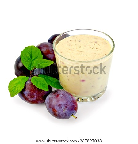 Milkshake in a glass with red plums and green leaves isolated on white background - stock photo