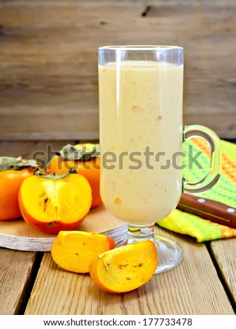 Milkshake in glass goblet with persimmons, napkin, knife on background wooden plank - stock photo