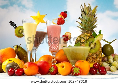 Milkshake or smoothie table with lots of summer fruits - stock photo