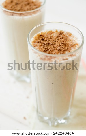 milkshake with chocolate topping in glass cup on white table - stock photo