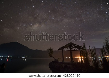 Milky way, a starry night sky over a lake.  Gazebo at foreground and mountain at background.  Location in Bali. - stock photo