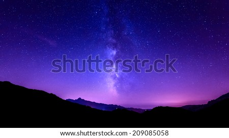 Milky Way Galaxy. Purple night sky stars above mountains - stock photo