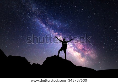 Milky Way. Night sky with stars and silhouette of a man with raised-up arms.  - stock photo