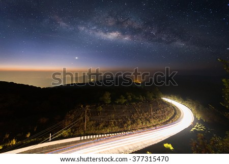 Milky way on night sky with lighting on the road at Doi inthanon Chiang mai, Thailand. - stock photo