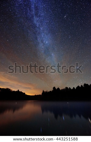 Milky Way over lake in Stowe, Vermont. - stock photo