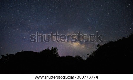 Milky way over the tree canopy (contains noise) - stock photo