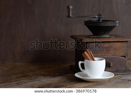 Mill for coffee with a white cup and cinnamon. Dark background. - stock photo