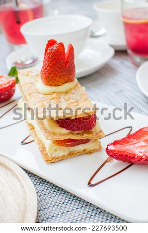 Mille feuille, puff pastry layered with strawberries and whipped cream in Tea set - stock photo