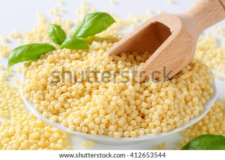 Millet grains with a wooden scoop - stock photo